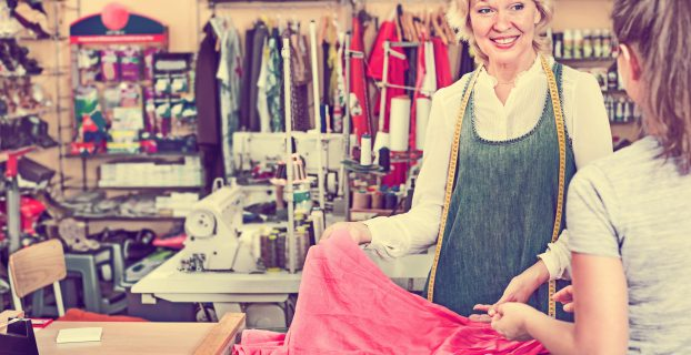 Cheerful mature woman tailor taking order from customer in the sewing workshop